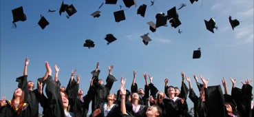Photo showing graduates throwing caps in the air.